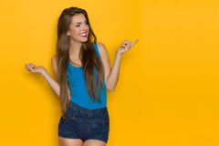 Amused Young Woman In Blue Tank Top Pointing. Smiling beautiful young woman in blue tank top and jeans shorts is pointing and looking away. Three quarter length royalty free stock photography