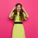 Amused Young Woman Is Holding Hands In Hair. Happy young woman in lime green dress is holding hands in hair and looking at camera. Three quarter length studio royalty free stock image