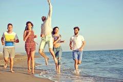 Amusement d'amis sur la plage sous la lumière du soleil de coucher du soleil Photographie stock