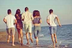 Amusement d'amis sur la plage sous la lumière du soleil de coucher du soleil Photos stock