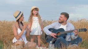 Amusement d'extérieur de famille, guitare de jeux de jeune homme tandis que sa femme et peu de fille mignonne dans les chapeaux d clips vidéos