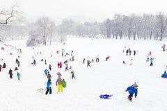 Amusement d'hiver, neige, famille sledding à l'horaire d'hiver Photos libres de droits
