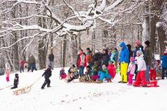 Amusement d'hiver, neige, famille sledding à l'horaire d'hiver Images libres de droits