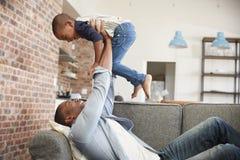Amusement d'And Son Having de père jouant sur Sofa Together photos libres de droits