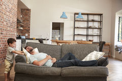 Amusement d'And Son Having de père jouant sur Sofa Together photographie stock libre de droits