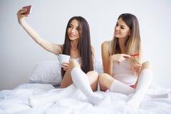 Amusement de causerie de deux amis au téléphone avec des amis par l'intermédiaire de la causerie visuelle dedans Photo libre de droits