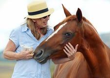 Amusement de détente de sourire de femme mûre de pays avec le cheval Photo stock