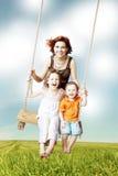 Amusement de famille Maman, fille, fils riant sur une oscillation Photo stock
