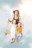 Amusement de famille Maman, fille, fils riant sur une oscillation Photos stock