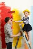 Amusement de famille pendant la peinture de mur Photo stock