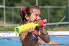 Amusement de fille avec le canon d'eau Image stock
