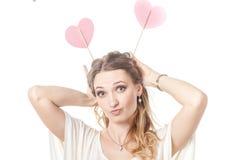 Amusement de fille posant avec deux coeurs dans le studio Photo stock