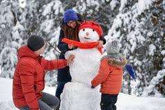 Amusement de l'hiver une fille, un homme et un garçon faisant un bonhomme de neige Photo stock