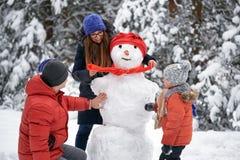 Amusement de l'hiver une fille, un homme et un garçon faisant un bonhomme de neige Image stock