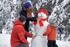 Amusement de l'hiver une fille, un homme et un garçon faisant un bonhomme de neige Photos libres de droits