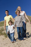 Amusement de mère, de père et de famille de deux garçons à la plage Photo stock