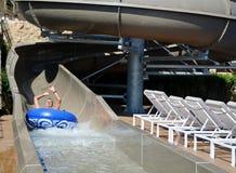 Amusement de parc d'Aqua - jeune homme montant en bas d'une glissière d'eau image stock
