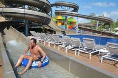 Amusement de parc d'Aqua - jeune homme montant en bas d'une glissière d'eau images stock