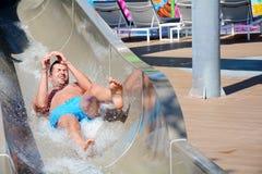 Amusement de parc d'Aqua - jeune homme montant en bas d'une glissière d'eau photographie stock libre de droits