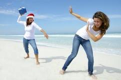 Amusement de vacances de Noël de femmes avec le présent à la plage Photographie stock