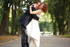 Amusement et amour - étreinte de nouveaux mariés sur le chemin en parc Images stock