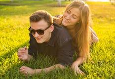 Amusement et concept d'amour avec un jeune couple se couchant dans l'herbe et le sourire Photos stock