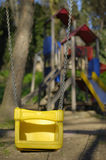 Amusement park in nature. A swing in focus and slide in background, among trees, warm tonnes Royalty Free Stock Photos