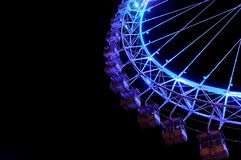 Big ferris wheel with festive blue illumination. Amusement park at night - big ferris wheel with festive blue illumination against night sky. Bottom view Royalty Free Stock Photo
