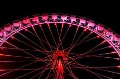 Big ferris wheel with festive red illumination against night sky. Amusement park at night - big ferris wheel with festive red illumination against dark night Stock Photo