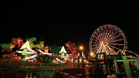 Amusement park at night with ferris wheel stock footage