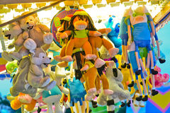 Amusement Park Prizes. Several rows of stuffed animals hang suspended above a brightly lit game at an amusement park Royalty Free Stock Photos