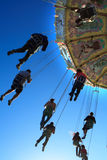 Amusement Park Ride. On a blue sky with spinning people Royalty Free Stock Photo