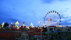 Amusement park at twilight time with ferris wheel. In motion stock video footage