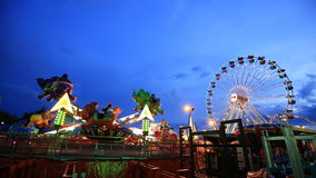 Amusement park at twilight time with ferris wheel. In motion stock video