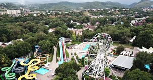 Amusement park. View of Ferris wheel and an Aqua Park with a drone. Shooting from height. Bright slides and colorful cabins in a green city Park. Central park stock video footage