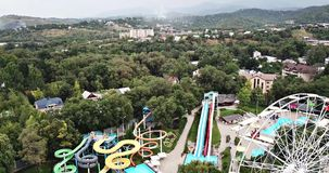 Amusement park. View of Ferris wheel and an Aqua Park with a drone. Shooting from height. Bright slides and colorful cabins in a green city Park. Central park stock video