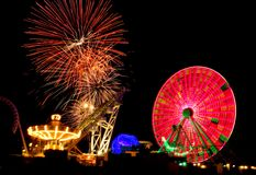 Amusement Ride & Fireworks. Amusement  ride in motion at night with fireworks in background Stock Photo