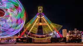 Amusement ride. Giant Ferris Wheel and Sea Ray amusement ride side by side in night time shot with long exposure Royalty Free Stock Images