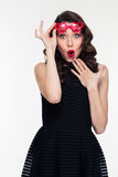 Amusing amazed curly young woman in red heart shaped glasses Stock Photos