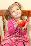 The amusing babe with an apple. The amusing babe on chair Royalty Free Stock Photo