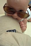 Amusing baby. Baby in black glasses with a big cap Stock Photos