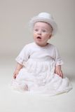 Amusing baby in retro hat. Amusing little baby in retro hat and elegant dress royalty free stock photography