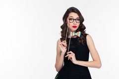 Amusing beautiful curly woman with fake bowtie and glasses booth Royalty Free Stock Photos