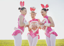 Amusing bunny outside. Three funny attractive females wearing costumes in field Stock Photos