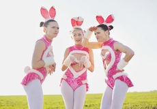 Amusing bunny outside. Three funny attractive females wearing costumes in field Royalty Free Stock Photos