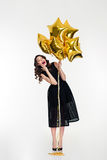 Amusing cheerful lovely curly girl  holding golden balloons Stock Photography