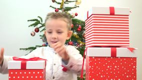 Amusing child hide, play and arrange gift boxes, Christmas tree in background. Amusing child hide, play and arrange present boxes, Christmas tree in background stock video