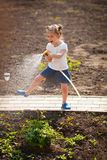 Amusing child watering flowers in the garden Stock Image