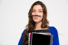 Amusing comical woman making funny face with pen. Amusing comical young woman holding folders and making funny face with pen over white background Stock Image