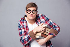 Amusing comical young male in round glasses holding books Royalty Free Stock Images